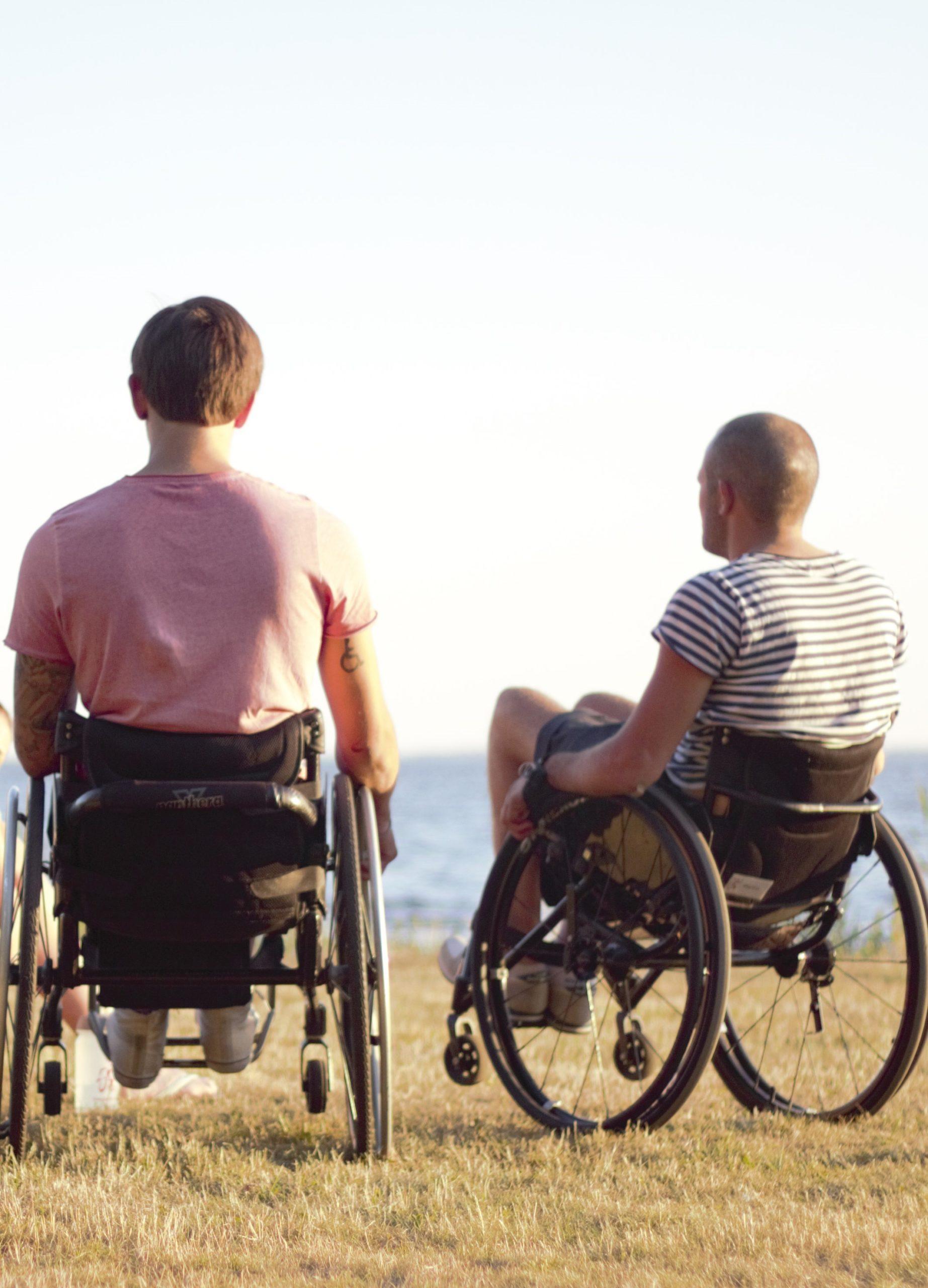 Två personer i rullstol som samtalar utomhus